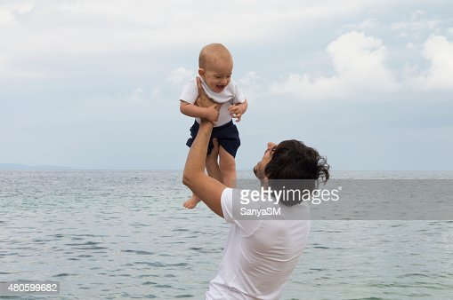 Father and son playing on the beach : Stock Photo