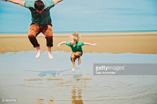 Father and son playing on the beach together