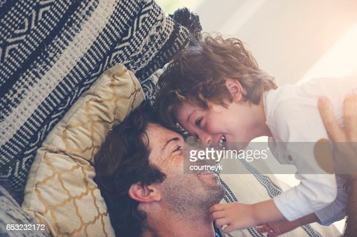 Father and son playing on the sofa. : Stock-Foto