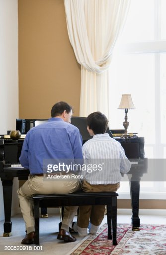 Father and son (11-13) playing piano, rear view