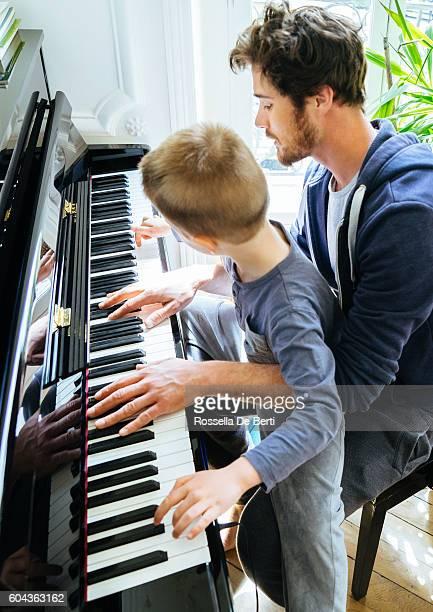 Vater und Sohn spielt zuhause Klavier spielen zu Hause