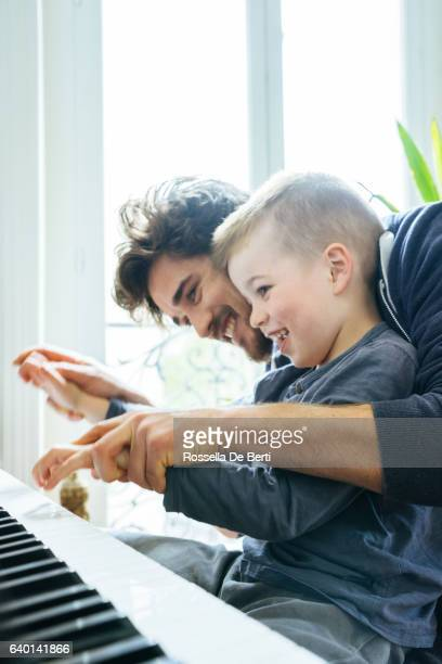 Father And Son Playing Piano Together At Home