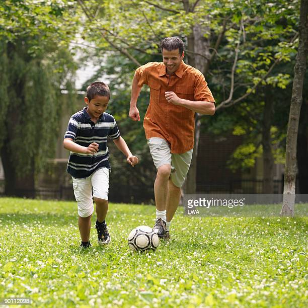 Father And Son Playing Soccer In Field