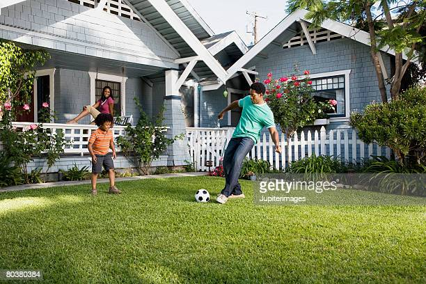 Father and son playing soccer in front yard