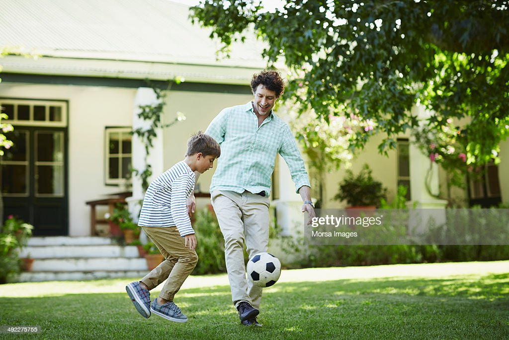 Father and son playing soccer in lawn : Stock Photo