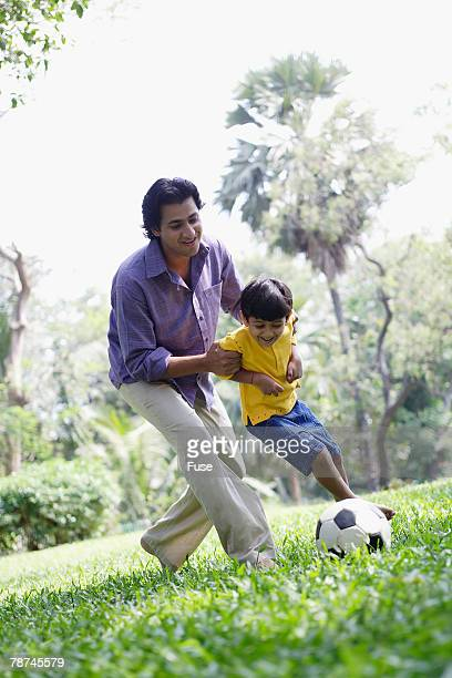 Father and Son Playing Soccer in Meadow