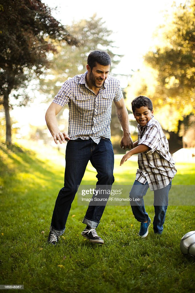 Father and son playing soccer together : Stock Photo