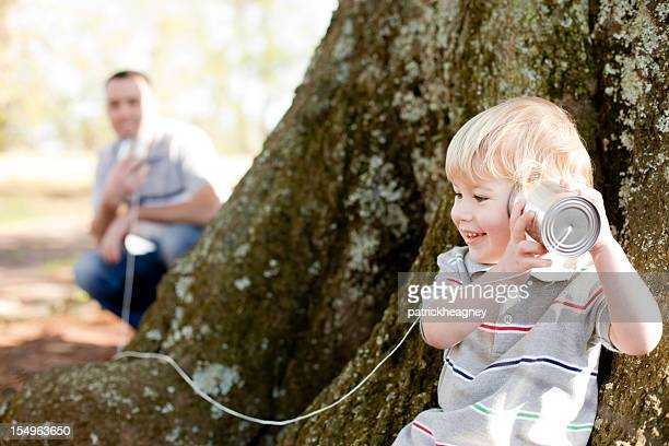 Father and son playing telephone in park