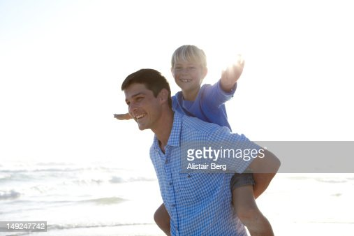 Father and son playing together on a beach : Stock Photo