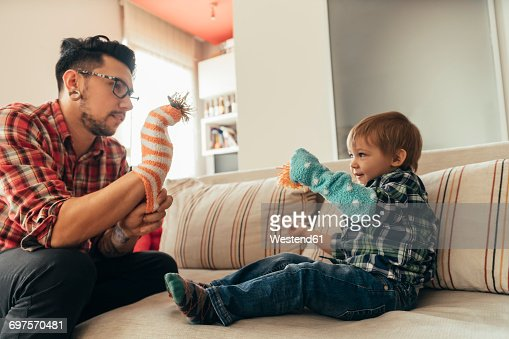 Father and son playing together on couch