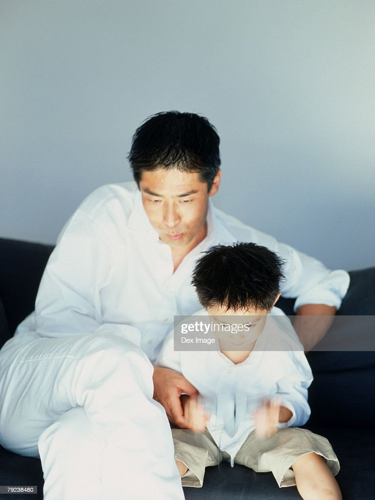 Father and son playing TV game : Stock Photo