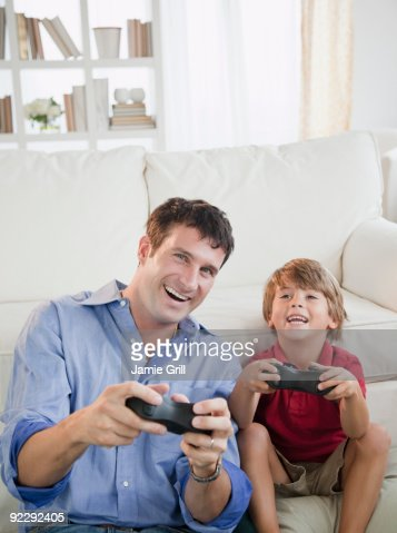 Father and son playing video games together : Stock Photo