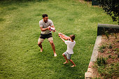 Boy playing water guns with father in backyard lawn. Father and son playing water gun fight outdoors.