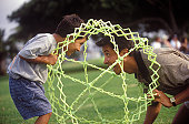 Father And Son Playing With A Hoberman Sphere In The Park