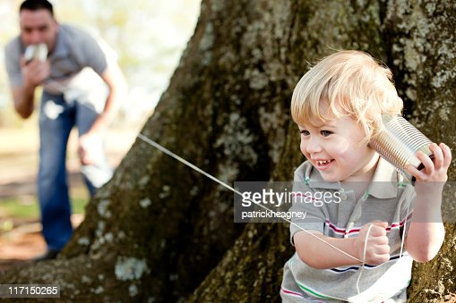 Father and son playing with a tin can telephone in the park : Stock Photo