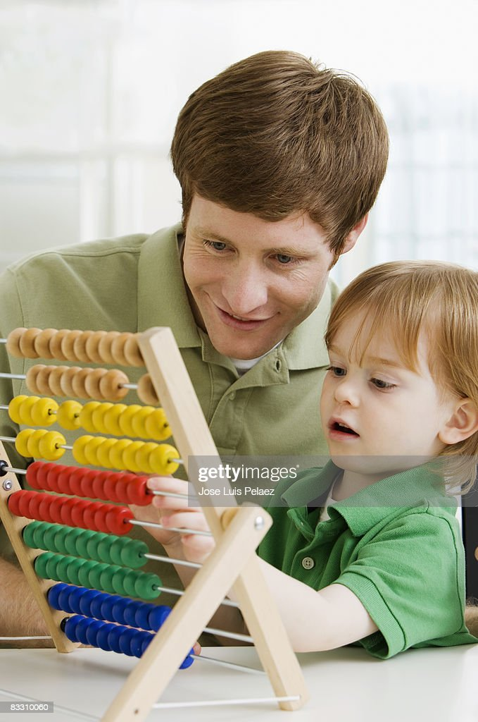 Father and son playing with abacus  : Stock Photo