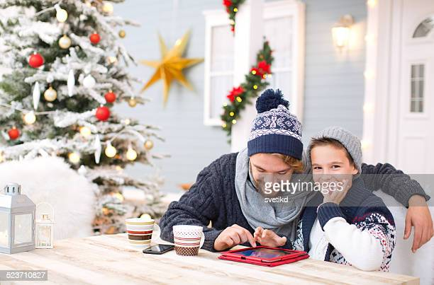 Father and son playing with digital tablet outdoors.
