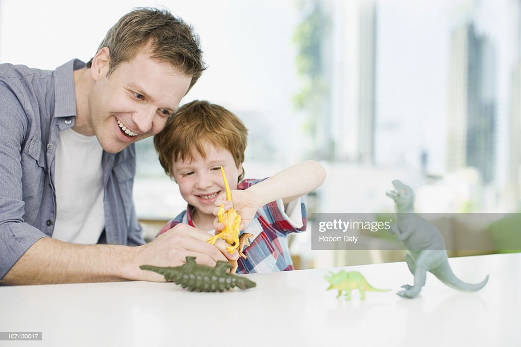 Father and son playing with plastic dinosaurs : Stock Photo