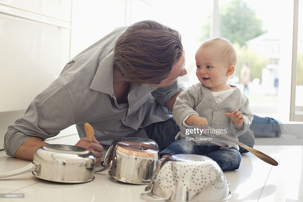 Father and son playing with pots and wooden spoons : Stock Photo