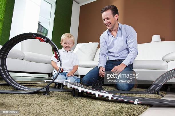 Father and son playing with race track