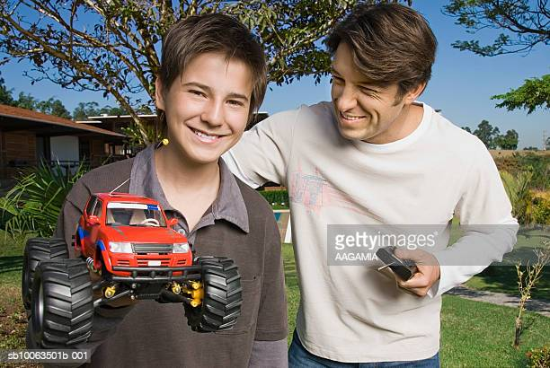Father and son (13-14) playing with RC car at garden, smiling