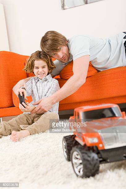 Father and son (6-7) playing with remote control car