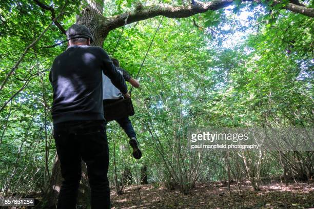 Father and son playing with rope swing in forest