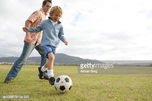 Father and son (6-7 years) playing with soccer ball on field, low angle view