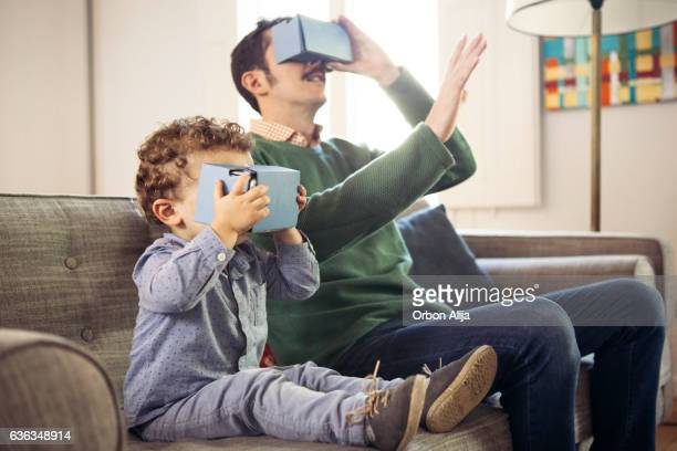 Father and son playing with virtual reality headsets.