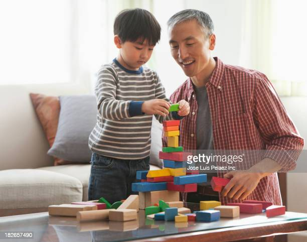 Father and son playing with wooden blocks