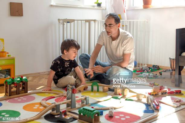 Father and son playing with wooden train set