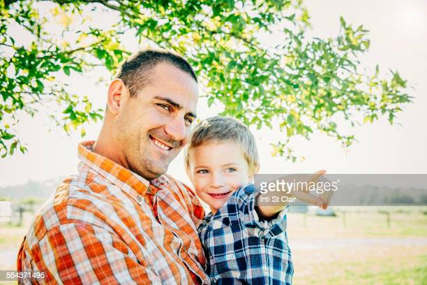 Father and son pointing on farm