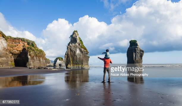 Father And Son Pointing Towards Three Sisters Famous Rocks At Tongaporutu North Taranaki New Zealand.