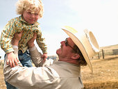 Cowboy holding up young son on ranch in Big Timber, Montana