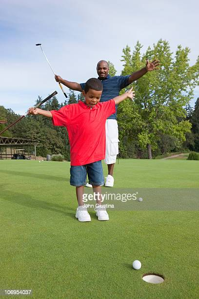Father and Son practicing putting.