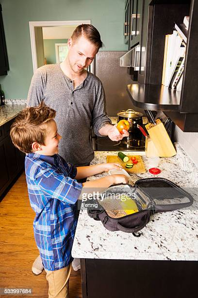 Father and son preparing a packed school lunch