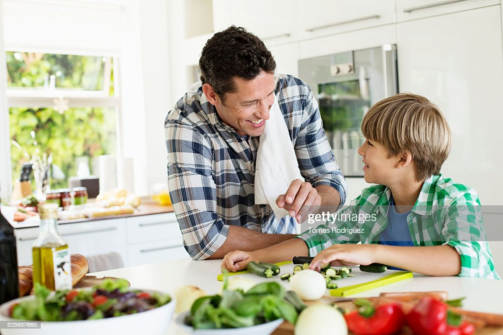 Father and son (6-7) preparing food in kitchen : Foto de stock