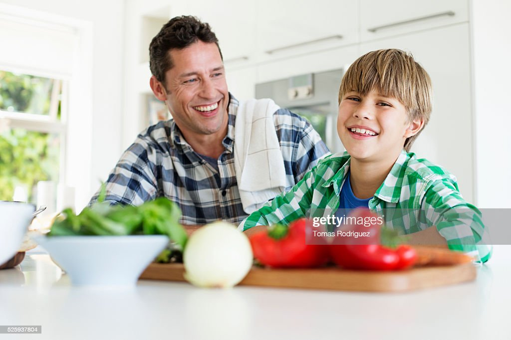 Father and son (6-7) preparing food in kitchen : Stock Photo