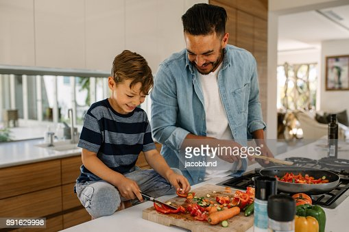 Father and son preparing food in kitchen : Stock Photo