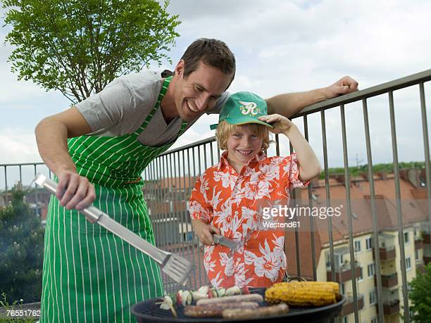 Father and son (8-9) preparing food on barbecue, smiling