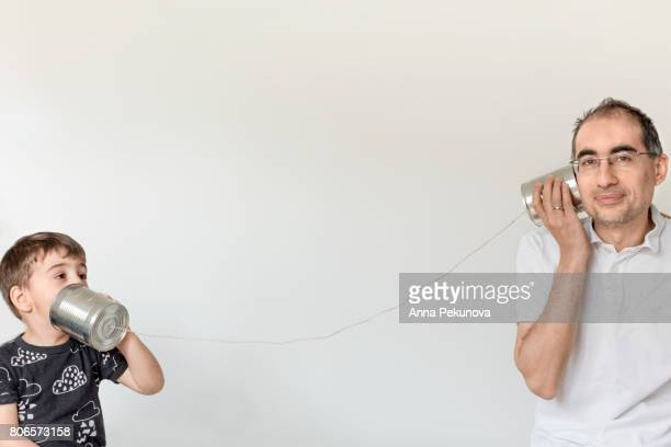 Father and son pretending to talk via self-made can- phone