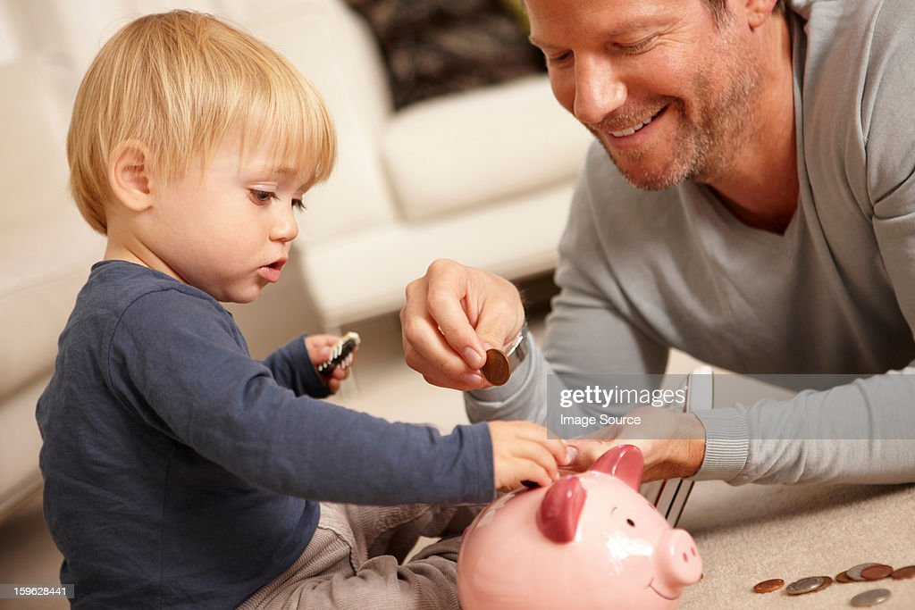 Father and son putting coins in piggy bank : Stock Photo