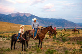 A father and son look over their ranch on horseback