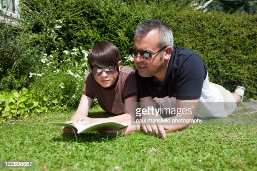 Father and son reading in garden : Stock Photo