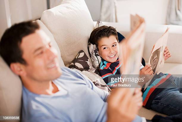Father and son reading newspaper on sofa