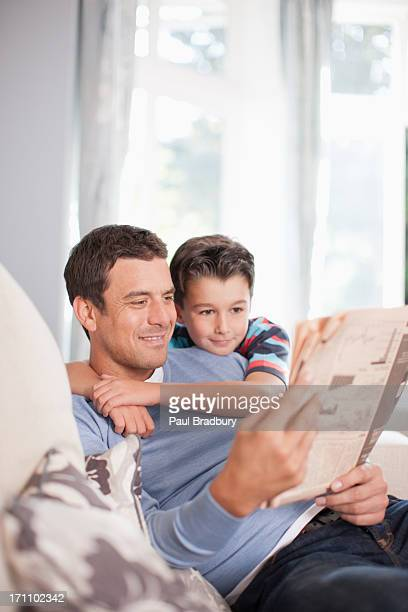 Father and son reading newspaper together