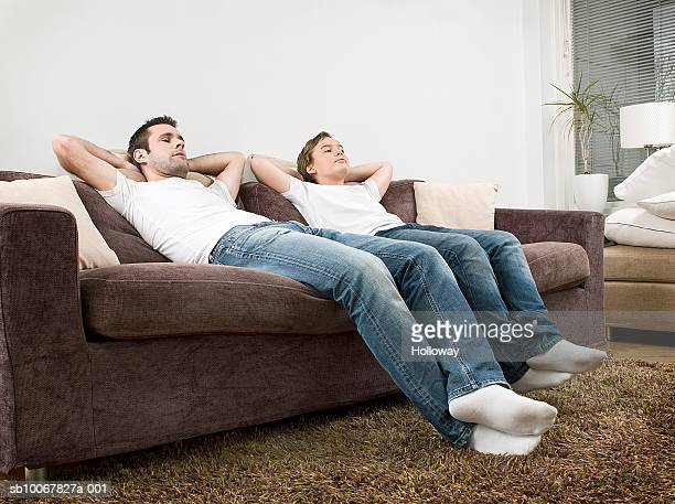 Father and son (10-11) reclining on sofa