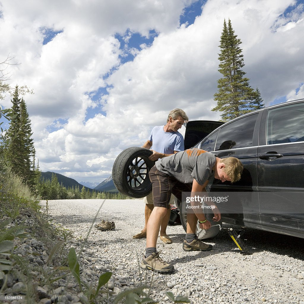 Father and son replace car tire on gravel mtn road : Stock Photo