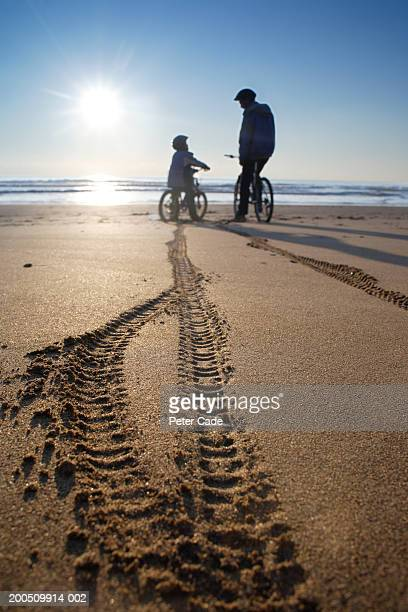 Father and son (6-8) resting on bikes on beach, tracks in foreground