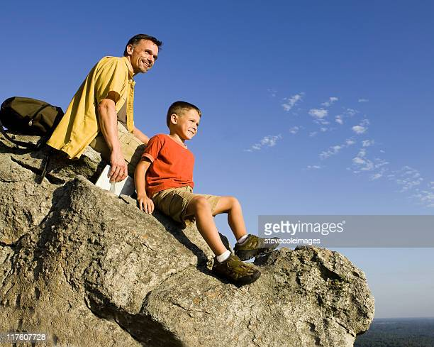 Father and Son Resting on Mountain Top